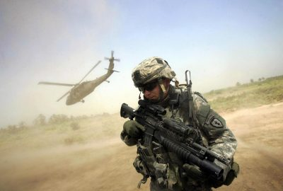 A US soldier from 1-501 Para-Infantry Regiment turns his back to the helicopter carrying Major General Rick Lynch, commander of US forces in central Iraq, as it takes off from a patrol base south of Baghdad, 29 August 2007. Radical Iraqi cleric Moqtada al-Sadr ordered his dreaded Shiite militia today to stop attacks on US-led forces as part of a six-month suspension of the militant group's activities. AFP PHOTO/DAVID FURST (Photo credit should read DAVID FURST/AFP/Getty Images)
